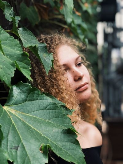 Thoughtful Teenage Girl Looking Away While Standing By Plants