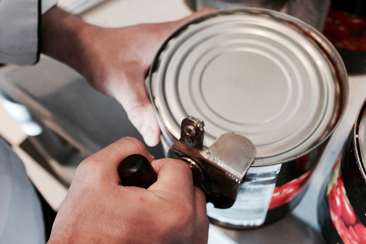 Cropped image of person using can opener at home