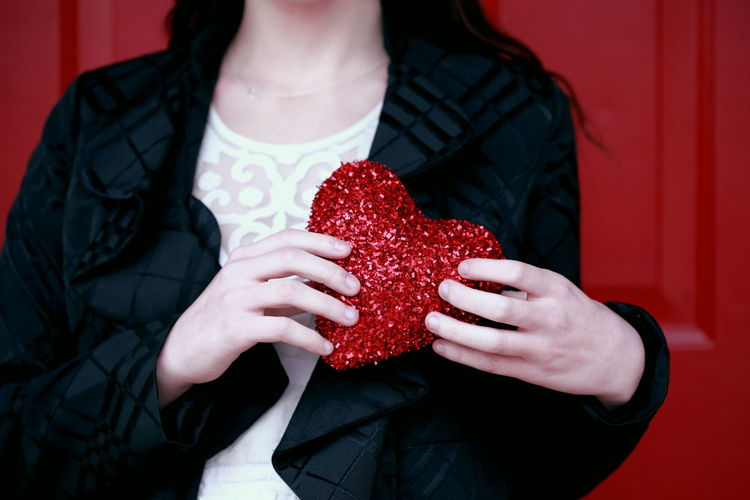 Midsection Of Woman Holding Red Heart Shape Against Door