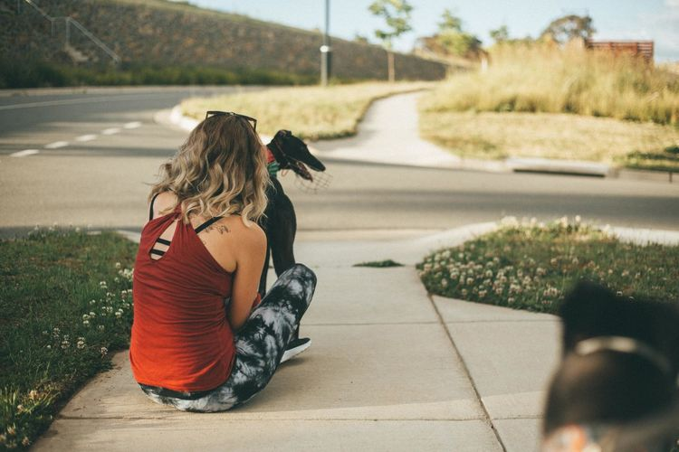 Rear view of young woman sitting with dog on footpath