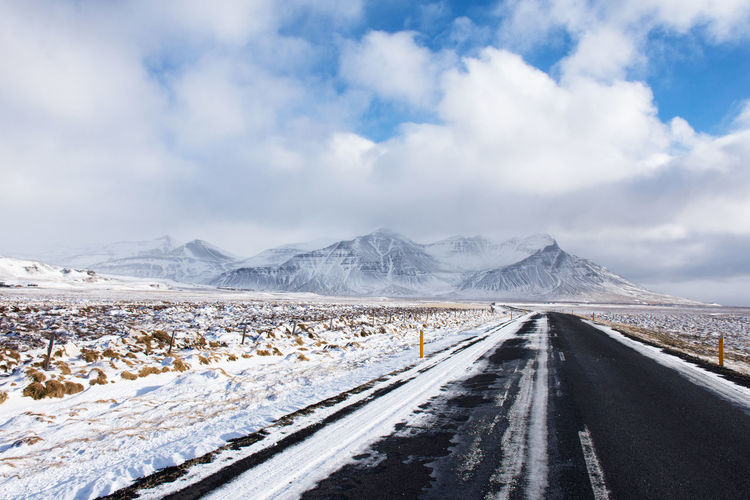 beautiful Iceland road heading to snow capped mountain with nice sky and cloud in sunny in winter. Iceland Transportation Beauty In Nature Cloud - Sky Cold Temperature Crash Barrier Day Diminishing Perspective Direction Environment Mountain Nature No People Non-urban Scene Road Road Trip Scenics - Nature Sky Snow Snowcapped Mountain The Way Forward Tranquil Scene Tranquility Transportation Winter
