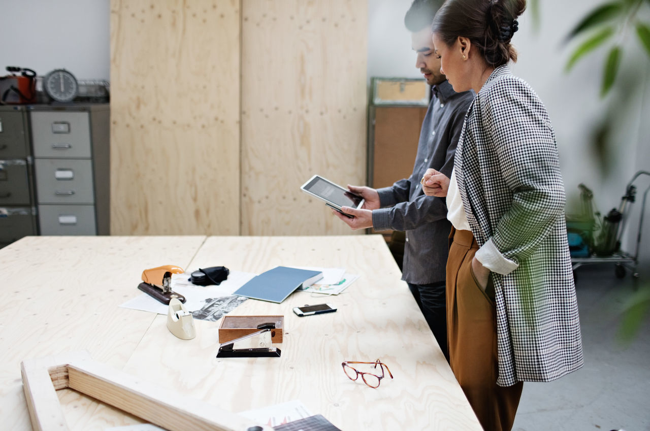 Businessman showing digital tablet to female colleague at table in meeting