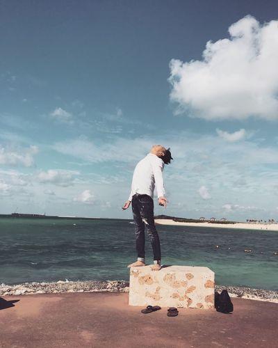 Man standing on beach against cloudy sky