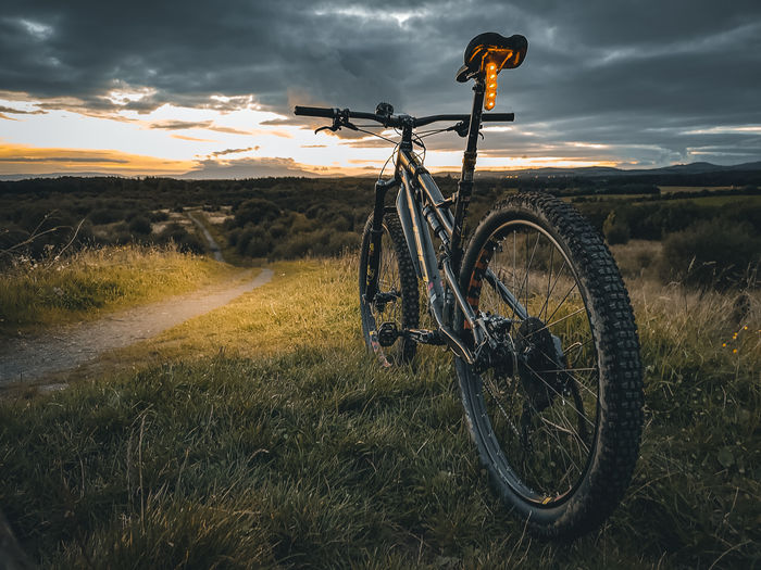 Bicycle on field against sky during sunset