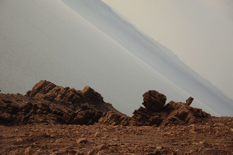Rock formations in desert at the sea against sky