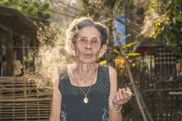 The relaxation of the elderly woman is smoking. Smoke Smoking This Is Masculinity Adult Adults Only Beautiful Woman Building Exterior Casual Clothing Day Front View Happiness Leisure Activity Looking At Camera Old One Person One Senior Woman Only Only Women Outdoors People Portrait Real People Senior Adult Senior Women Smiling Water My Best Travel Photo A New Beginning EyeEmNewHere 17.62°