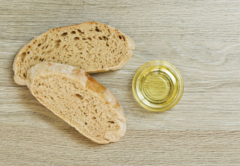 two slices of Ciabatta bread and a bowl of extra virgin oil on a wooden textured background Basic Bread Food Food And Drink Freshness Healthy Eating Italian Food Itialian No People Oil Table