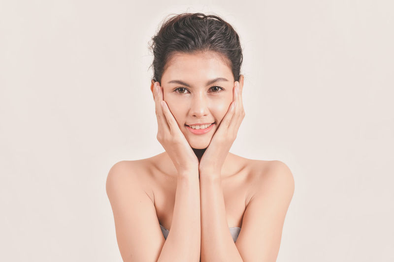 Adult Beautiful Woman Beauty Body Care Front View Hand Headshot Human Body Part Human Face Indoors  Looking At Camera One Person Portrait Shirtless Smiling Studio Shot White Background Women Young Adult Young Women