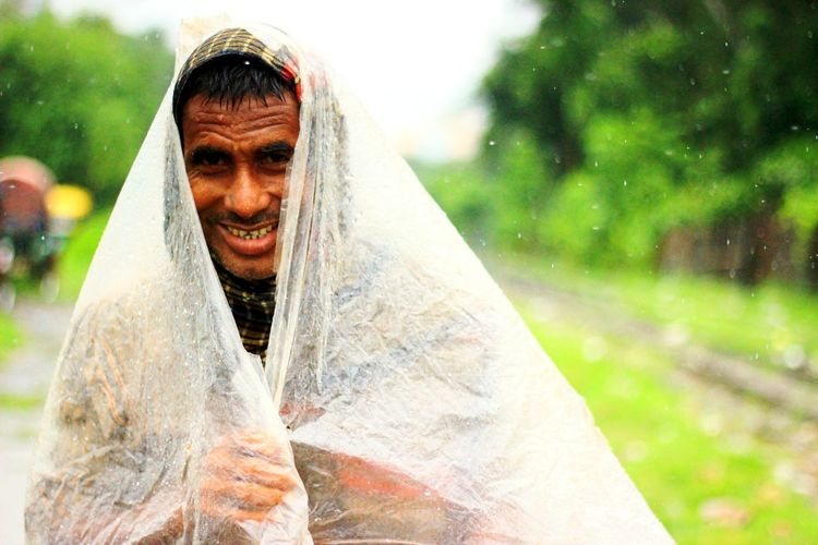 Close-Up Portrait Of Man Covered With Plastic During Rainy Season