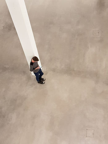 Alone From Above  Jeans Mobile Phone Pilar Waiting Day Galery High Angle View Indoors  Leaning Men One Person People Real People Sad Space Texting Young Man