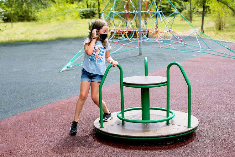 Girl wearing mask playing on carousel at playground