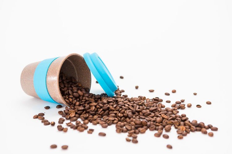 Overturned White Coffee cup with Coffee Beans Inside on a White Background White Background Studio Shot Roasted Coffee Bean Still Life Indoors  Food And Drink Coffee - Drink Large Group Of Objects Coffee Close-up Food No People Freshness Brown Copy Space Abundance Caffeine Roasted Container