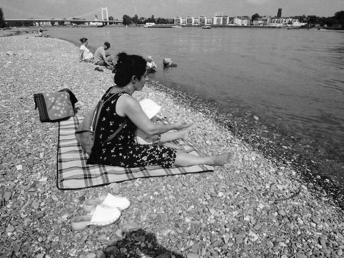 Woman with a baby siitting on a stony beach at the ruver rhine in Cologne. Lifestyles Real People Outdoors Beach Sitting Leisure Activity Water Day Sand Sea Women People Adult Black & White German Blackandwhite Monochrome Monochrome Photography Rhein Köln Rhine Cityscape Cologne Mother & Daughter Black And White Photography