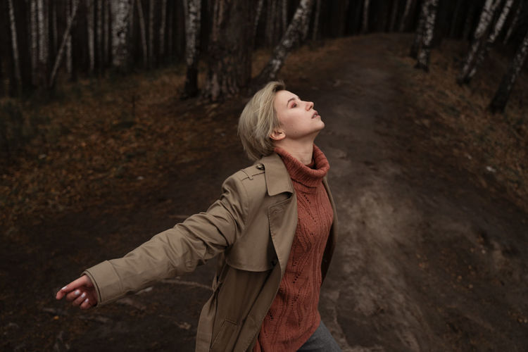 Young woman looking up in forest