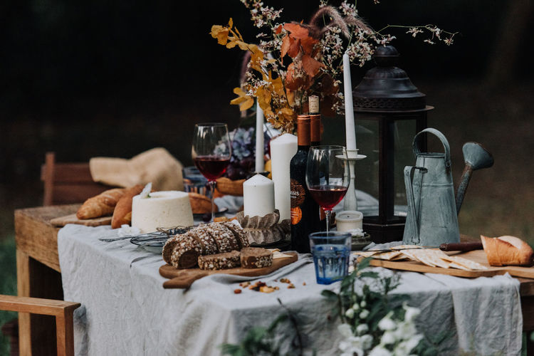 Food and drink with flowers on table in yard