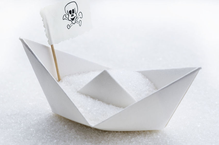 Sugar in a paper boat. Conceptual image. Sugar addiction. Copy space. Addiction Bakery Blood Glucose Level Brown Sugar Carbohydrates Children Obesity Conceptual Photography  Copy Space Danger Deseas Diabetes Diet Glycemic Index Harmful Obesity Overweight Paper Boat Skull Flag Skulls And Bones Sugar Sugar Cubes Sweet Food Table Sugar Tooth Decay White Sugar