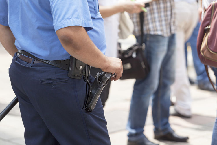 Police officer on duty Adult Adults Only Arrest Casual Clothing Crime Day Handcuffs  Handgun Hands Behind Back Human Body Part Jeans Justice - Concept Law Legal System Men Only Men People Pistol Police Force Police Uniform Punishment Standing Weapon Young Adult