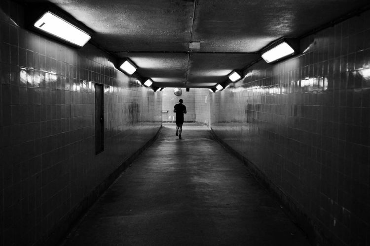 Rear view of person walking in illuminated tunnel