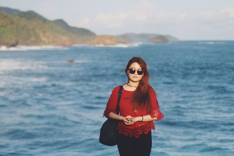 Portrait of young woman wearing sunglasses standing at beach