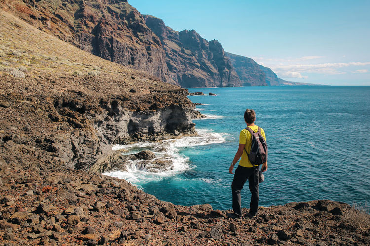 Rear view of man with a backpack standing on rock by sea against sky