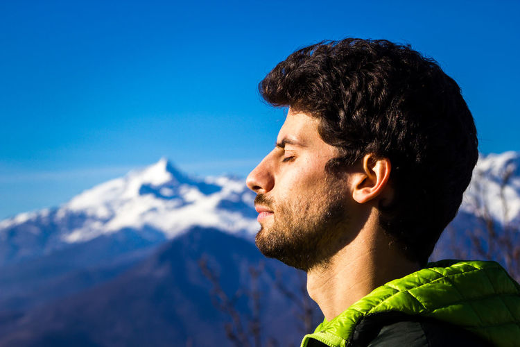 Portrait of young man against sky and mountain
