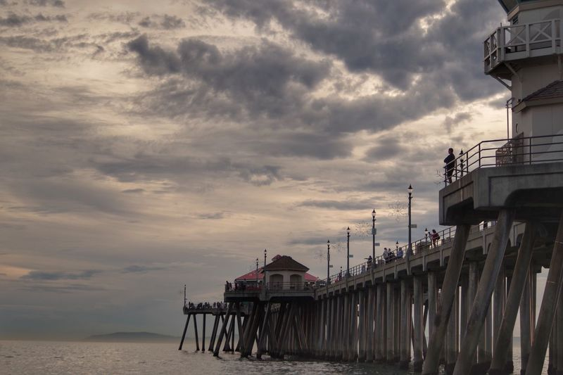 Pier over sea at huntington beach against cloudy sky during sunset