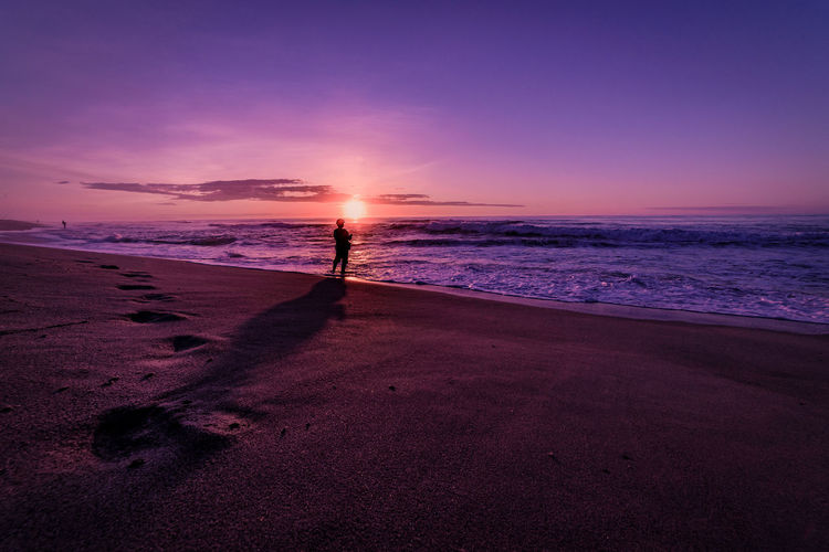 Silhouette man standing on shore at beach against purple sky during sunset