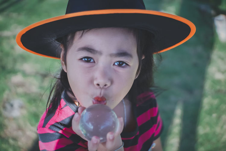 My little witch, Halloween day.. Acting Cosplay Dress Glass Ball Halloween Hat Sunlight Asian Girl Ball Glass Black Hair Day Face Girl Kid Little Girl Magic Orange Color Outdoors Playful Portrait Skull Smilling Witch Wonder Young Adult