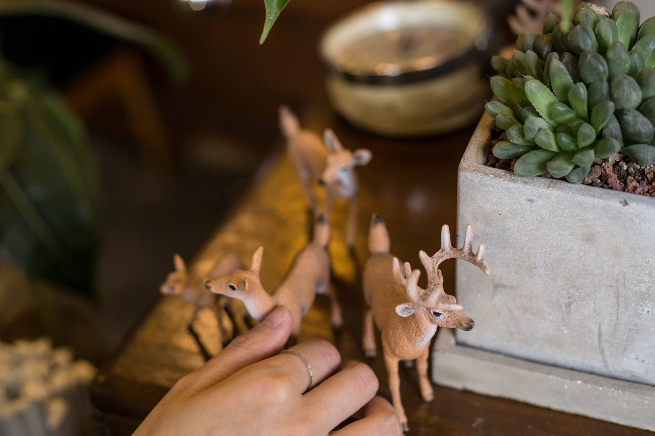 Close-up of hand by deer figurines on table