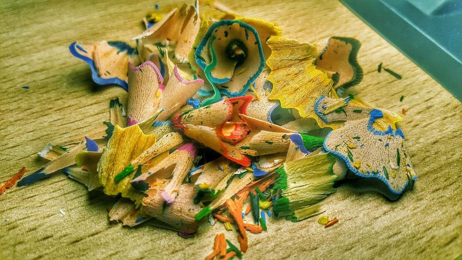Close-Up Of Colorful Pencil Shavings On Wooden Table