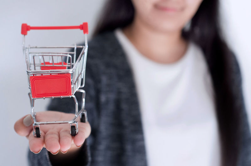 Shopping Trolley Adult Cart Close-up Connection Drink Females Focus On Foreground Front View Holding Human Body Part Indoors  Lifestyles Midsection One Person Online  Real People Selective Focus Technology Women Young Adult