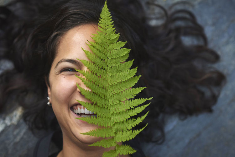 Close-up portrait of young woman with plants