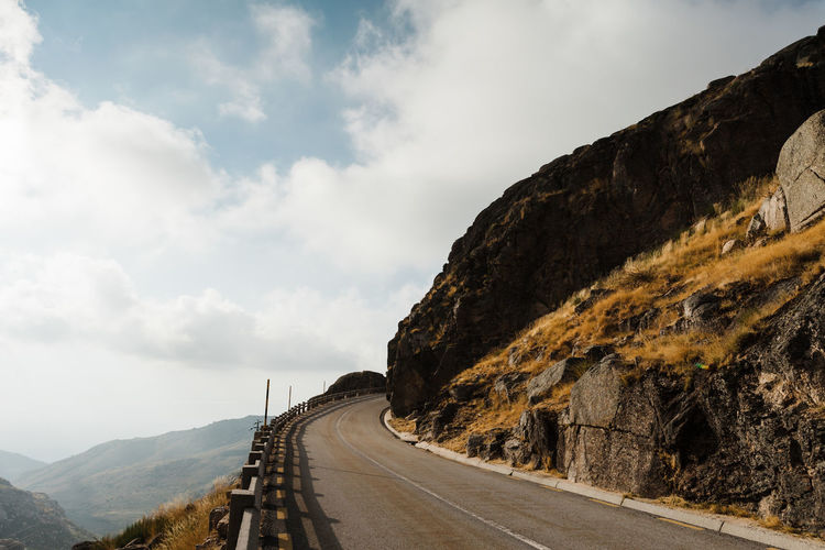Empty road by mountains against sky
