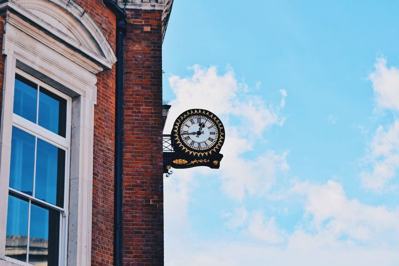 Low angle view of clock against sky
