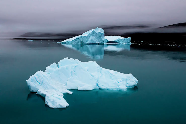 Beautiful blues of icebergs in Disko Bay, Greenland Water Ice Glacier Frozen Cold Temperature Iceberg Tranquility Scenics - Nature Tranquil Scene Winter Environment Sea Nature No People Landscape Beauty In Nature Day Iceberg - Ice Formation Floating On Water Turquoise Colored Frozen Water Arctic Greenland Fog Mist