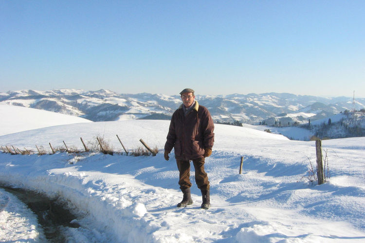 Mature man standing on snow covered hill against sky