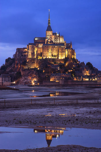 Le mont Saint Michel in France at dusk Mont Saint-Michel Mont Saint Michel Le Mont-Saint-Michel France Normandie Dusk Dawn Twilight Illuminated Medieval Ancient Place Of Worship Low Tide Reflection Landmark Travel Destinations Famous Place Building Exterior Built Structure Architecture Building The Past Religion Outdoors