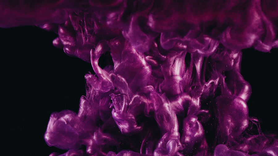 Close-up of purple ink in water against black background