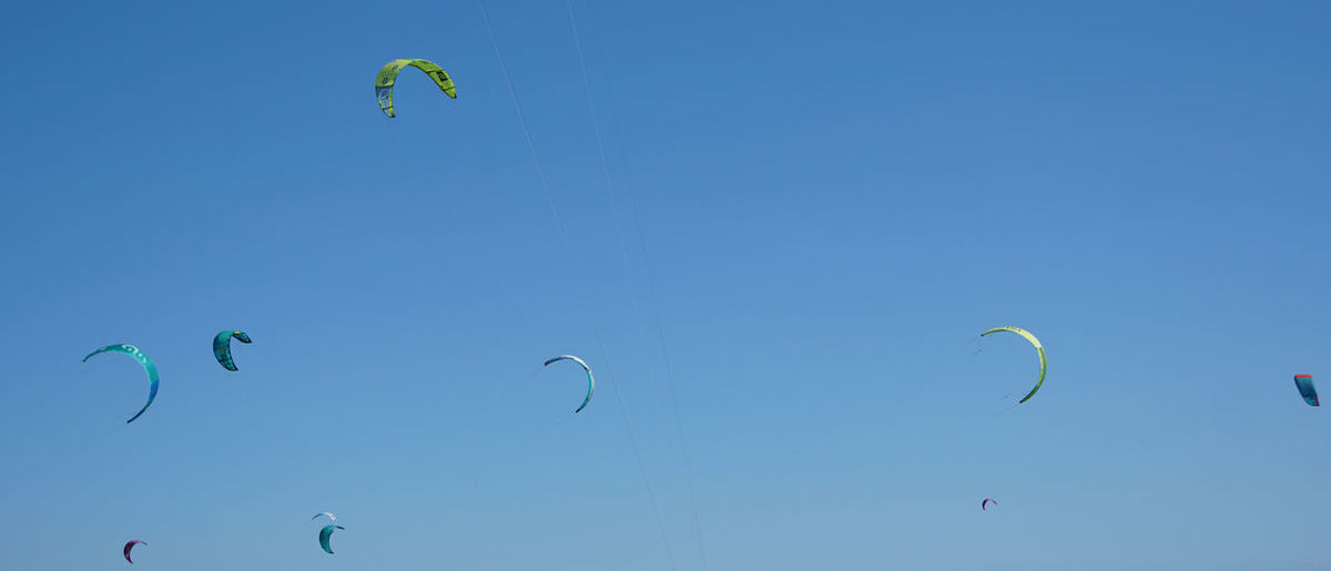 Low angle view of people flying against clear blue sky