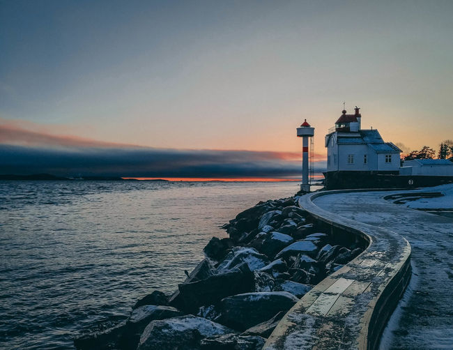 Lighthouse by sea against sky during sunset