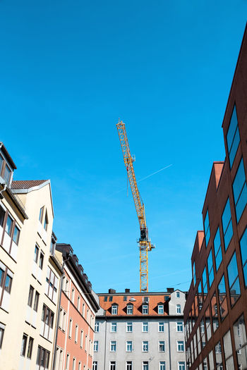Built Structure Architecture Building Exterior Sky Building Blue City Clear Sky Crane - Construction Machinery Day No People Low Angle View Machinery Window Residential District Construction Industry Copy Space Development Tall - High Outdoors Construction Equipment Apartment House Building Housing