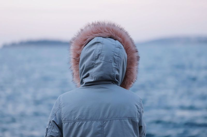 Rear view of woman looking at sea against sky during winter