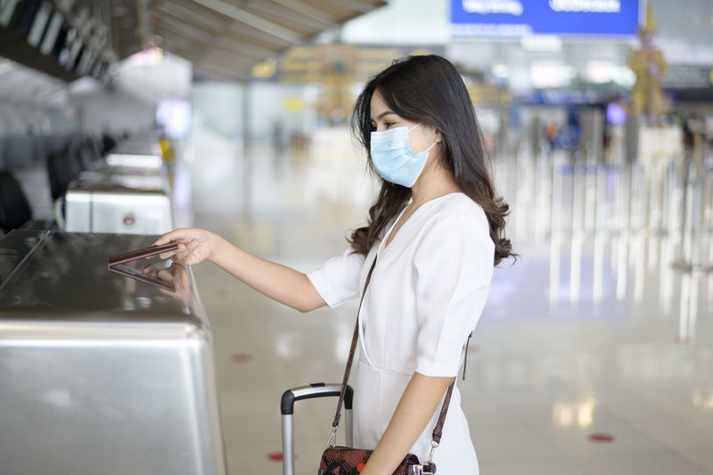 Side view of woman wearing mask giving passport standing at airport