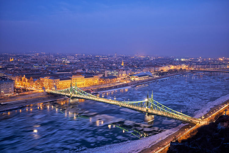 Bridge over river in illuminated city against sky