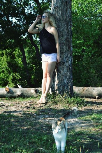 Full length of young woman standing on tree trunk in forest