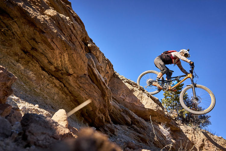 Low angle view of man riding bicycle on rock