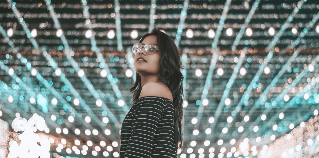 Young woman standing against illuminated ceiling