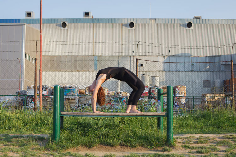 Woman Doing Yoga On Bench Against Wall
