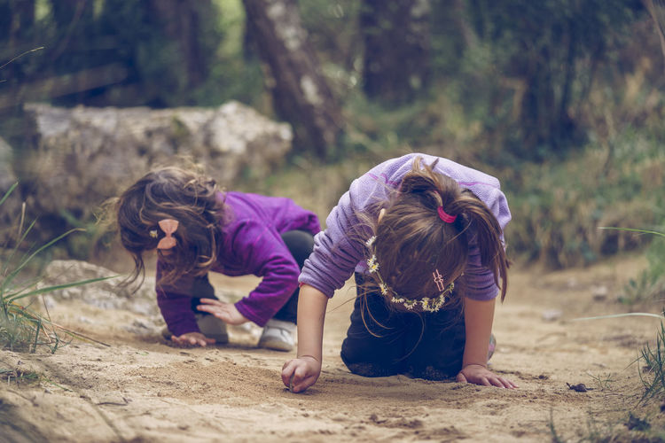 Two little girls playing and heading with the sand. active family holidays with children.