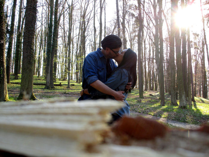 Couple Kissing Against Trees In Forest